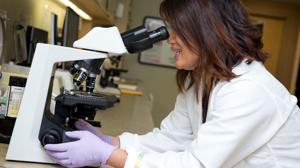 Female medical lab worker with microscope